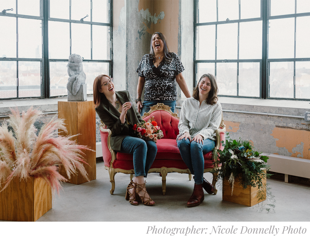 Nicole Donnelly Photography image of Ashland Addison Weddings & Events Staff. Three Wedding & Events Stylists are sitting on a couch, laughing.